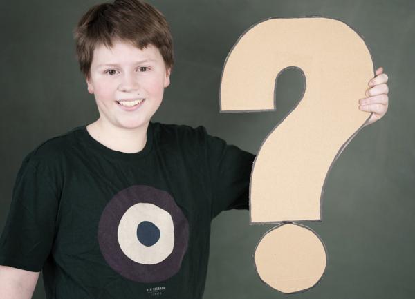 Junge hält großes Fragezeichen